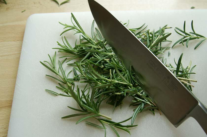 Rosmarin wird mit dem Messer zerkleinert